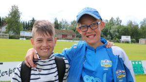 Två pojkar håller om varandra vid en fotbollsplan.