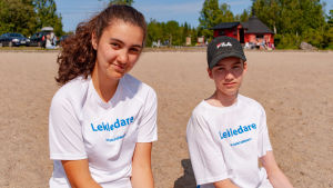 Två tonåringar, en flicka och en pojke, iklädda lekledarskjortor.