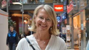 En leende kvinna i vit skjorta.
