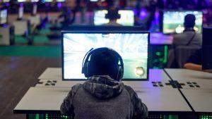 Ung gamer framför datorskärm.