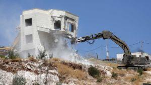 En israelisk grävmaskin river ner ett hus i en palestinsk by i östra Jerusalem i juli 2019