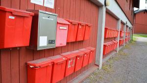 en lång rad med röda brevlådor utan namn