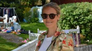 Kvinna i solglasögon står och ler på en innergård.