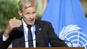 Jan egeland, chef för det humanitära arbetet i Syrien, gestikulerar och talar framför FN:s flagga.