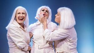 Skådespelarna Anna Hultin och Hellen Willberg håller fast Cecilia Paul emellan sig och nyper henne över kinderna. De är alla klädda i vitt.