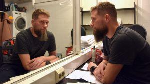 Magnus Betnér framför en spegel.