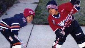 Minnan pojat poseraa jääkiekkomailojen kanssa lapsina.