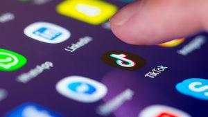 Ett finger syns över TikToks ikon på en smarttelefon.