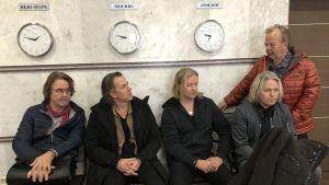 Fem medelåders män sitter på en bänk under tre klockor som visar olika tider. Ryska skyltar syns ovanför klockorna.