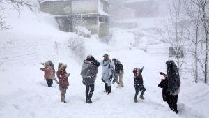Människor står ute i snöövändet i Murree, 60 kilometer norr om Islamabad i Pakistan.