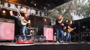 En musikgrupp spelar på en scen. En gitarrist har benet upp i luften trots att han spelar. Sångaren står i mitten och bredvid honom också två ytterligare gitarrister eller basister.