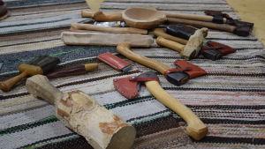 Yxor och andra verktyg för träslöjd utspridda på en trasmatta.