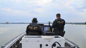 Två sjöbevakare som kör en båt.