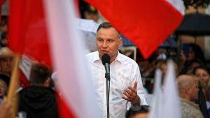 Andrzej Duda pratar in i en mikrofon vid ett talarpodium. I förgrunden syns den polska flaggan.