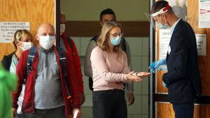 En man desinficerar en kvinnas händer med sprayflaska. Bakom kvinnan står andra människor på rad. Personerna ska rösta i Polens presidentval.