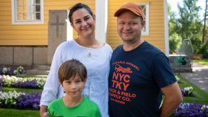 En familj, mamma i vit skjorta och mörkbrunt hår, pappa i orange keps och blå t-skjorta och liten son i grön t-skjorta och mörkt hår.