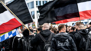 Svartklädda män men flaggor