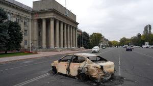 En utbränd bil på gatan framför en palatsliknande byggnad