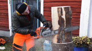 En man skalar en stock med en motorsåg.