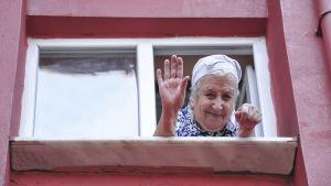 Glad äldre kvinna tittar ut genom fönstret och vinkar.
