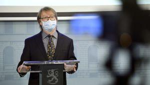 Olli Vapalahti talar framför kameror iklädd munskydd.