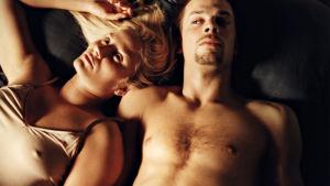 Huvudpersonerna i Levottomat ligger halvnakna på en säng.