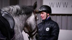 Jerry Kvarnström står bredvid en häst.