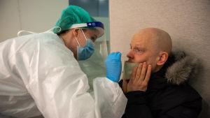 Sairaanhoitaja ottaa näytteen korona-testistä mieheltä. Koronatestiasema. Messukeskus. 19.3.2021.