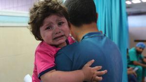 Ett gråtande barn i förs i famnen på en man i ett sjukhus.