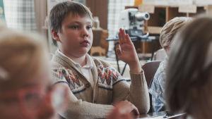 Ruskeaan villatakkiin pukeutunut poika istuu pulpetissa ja viittaa kädellään.