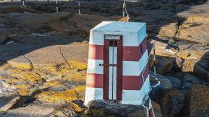 Entinen huussina toiminut nelikulmainen, punavalko-raidallinen rakennus kalliolla.