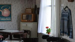 Ett gammaldagsinrett café. Bord och stolar i mörkt trä och ljusa, blommiga tapeter.