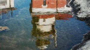 Veden pinnassa kuvajainen majakasta.