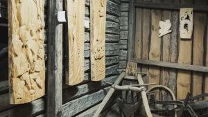 Tre stycken träreliefverk hänger på väggen i en gammal lada. På golvet intill finns gammal släde och seldon som tillhör häst.