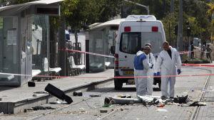 Israeliska poliser undersöker platsen i Jerusalem där en palestinier körde in i en folkmassa med bil den 5 november 2014.