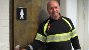Göran Burman med handen på dörrhandtaget till herrtoalett inomhus