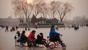 En grupp människor njuter av isen på sjön Houhai i Peking på ett kreativt sätt.