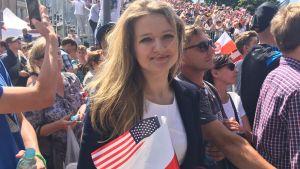 En ung polsk kvinna följer med Trumps tal på Krasinski-platsen i Polen.