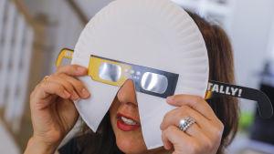 En förälder provar på solförmörkelseskydd som hon förstorat med hjälp av en papptallrik. Skyddena ska användas av en förskoleklass i Gerogia, USA under solförmörkelsen som inträffar den 21 augusti.