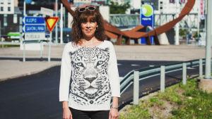 En kvinna poserar framför ett konstverk i staden Sankt Michel.