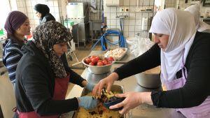 Kvinnor med huvuddukar lagar mat i ett storkök.