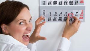 Kvinna ser i kalendern att det är fredagen den 13.