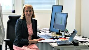 En kvinna iklädd klänning och kavaj, sitter vid ett skrivbord med många dataskärmar. Hon är en forskare.