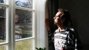 Björn Skifs tittar ut genom sitt fönster i den gamla prästgården där han bor.