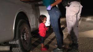 Ett barn från Honduras gråter då hennes mor kroppsvisiteras vid gränsen mellan USA och Mexiko