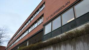 Bild på S:t Olofsskolans tegelbyggnad utifrån, skolans namn står på väggen.
