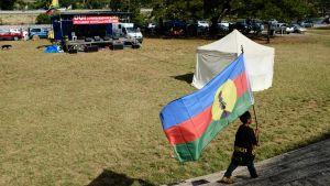 Pojke med flagga som stöder självständighet i Nya Kaledonien