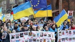 En bild på människor som går i ett demonstrationståg i Ukraina. Ukrainska flaggor syns i tåget.
