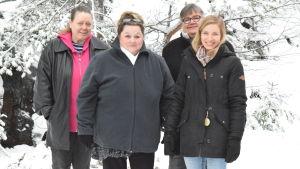 Fyra kvinnor står på en rad ute i vintrigt landskap.