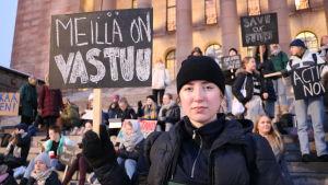 """Den svartklädda Ilon Adlercreutz har en skylt med texten """"Meillä on vastuu"""" (Vi har ett ansvar)."""